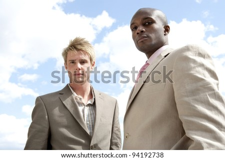 Portrait of two businessmen standing against a blue sky.