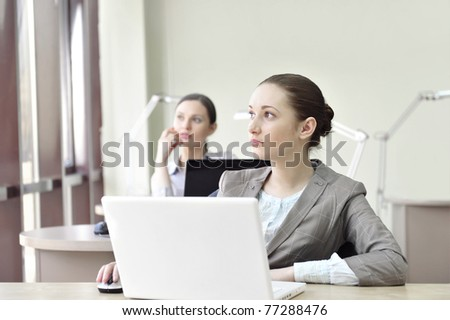 Portrait of two businesswomen listening attentively. Office background.