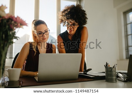 Portrait of two businesswomen looking at laptop and discussing new project in office. Young business colleagues discussing work in the office.