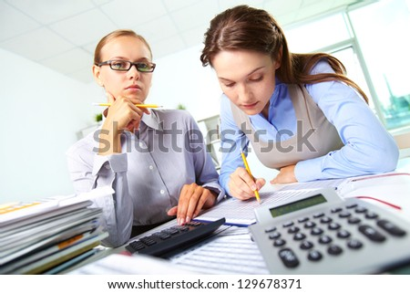 Portrait of two businesswomen working with papers in office