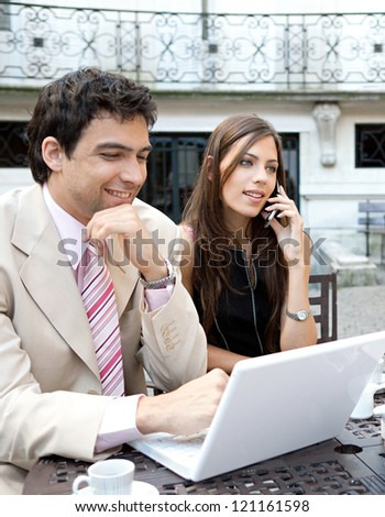 Portrait of two busy business people having a meeting in a coffee shop terrace in a classic city financial district, using technology and smiling.