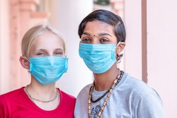 portrait of two Caucasian and African girls in protective medical masks, coronavirus concept. multinational friendship. lockdown is over, the end of the epidemic. quarantine finish.