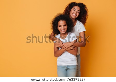 Portrait of two cheerful african sisters hugging and looking at camera isolated over orange background