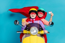 Portrait of two cheerful elderly retired pensioners riding moped using card buy order isolated over bright blue color background