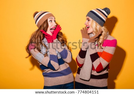 Portrait of two cheery girls dressed in winter clothes standing and looking at each other isolated over yellow background #774804151
