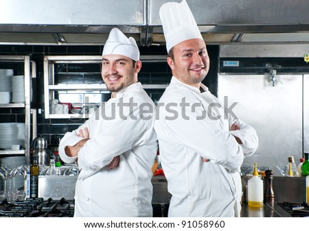 Portrait of two chefs standing back to back smiling and holding kitchen utensil