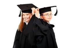 Portrait of two children in a graduation gown. Education. Isolated over white.