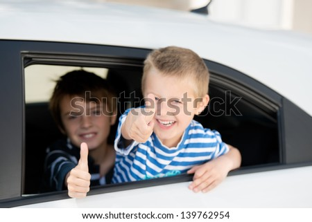 Portrait of two children inside the car showing thumbs up sign - stock photo