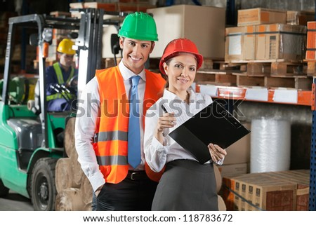 Portrait of two confident young supervisors with book clipboard at warehouse