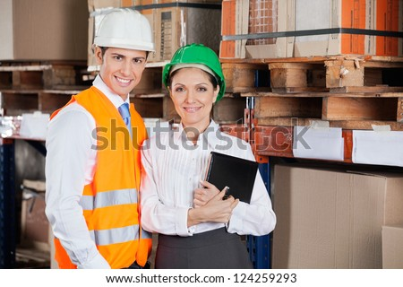 Portrait of two confident young supervisors with book standing at warehouse