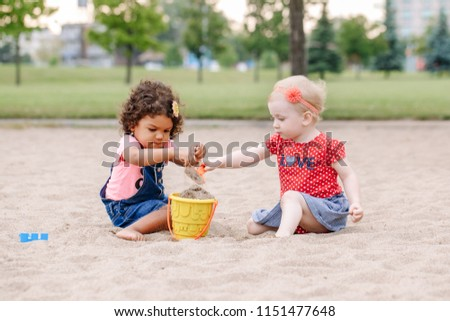 Portrait of two cute Caucasian and hispanic latin toddlers babies children sitting in sandbox playing with plastic colorful toys. Little girls friends having fun together on playground.