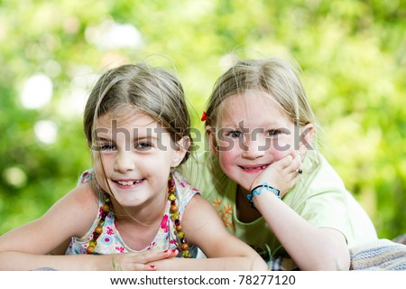Portrait of two cute girls having rest in park on summer day