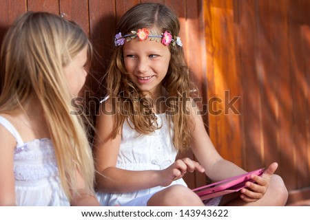 Portrait of two cute kids playing with digital tablet outdoors.
