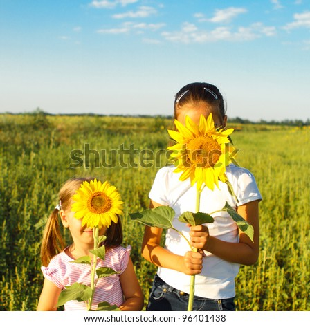 Portrait of two cute little girls hiding behind sunflowers on sunny day