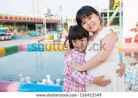 Portrait of two cuties hugging by the pool full of rubber ducks