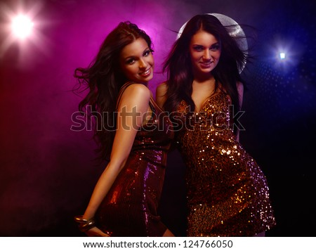 Portrait of two dancing girls on disco party
