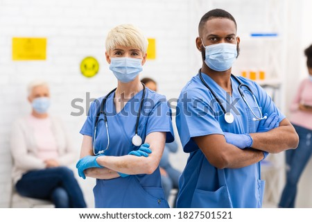 Portrait Of Two Diverse Doctors In Protective Masks Posing Looking At Camera Standing In Hospital Waiting Room With Patients. Medical Clinic Staff, Physician Doctor And Nurse Profession Concept