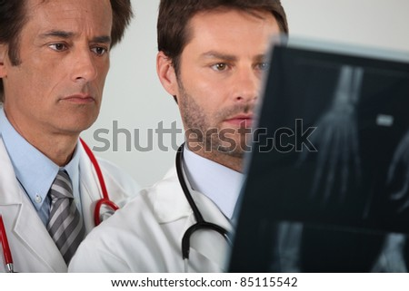 portrait of two doctors examining X-rays