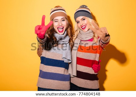 Portrait of two excited girls dressed in winter clothes standing and showing peace gesture isolated over yellow background #774804148