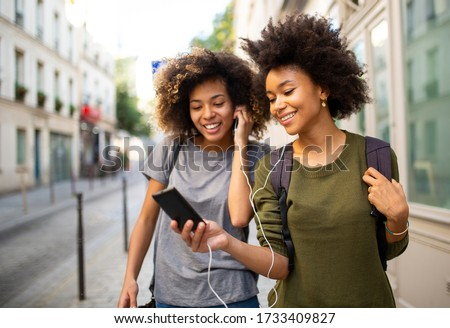 Portrait of two female black friends walking in city with mobile phone listening to music with earphones Сток-фото ©