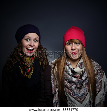 Portrait of two female friends in playful mood against grey background