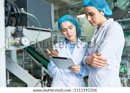 Portrait of two female specialists wearing lab coats working at modern food factory and checking production process via digital tablet standing by power units in workshop, copy space