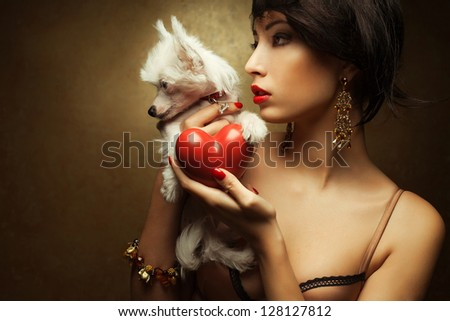 Portrait of two friends:  fashionable model with sexy red lips holding red heart (love symbol) and little white chinese crested dog. Both posing over golden background. Profile. Close up. Copy-space.