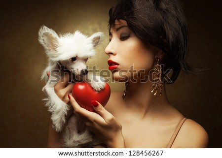 Portrait of two friends:  fashionable model with sexy red lips holding red heart (love symbol) and white little chinese crested dog. Both posing over golden background. Profile. Close up.