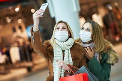 Portrait of two friends shopping together using smartphone and wearing a mask