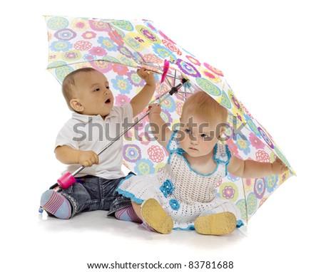 Portrait of two funny kids sitting under umbrella