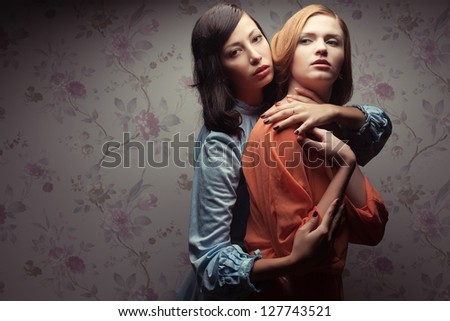 Portrait of two gorgeous girlfriends in blue and orange dresses in a hotel room. Vintage style. Copy-space. Studio shot