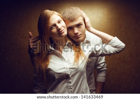 "Portrait of two gorgeous smiling red-haired (ginger) fashion twins in white shirts posing over golden background together. Brother is going to ""shoot"" his sister. Studio shot."