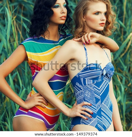 Portrait of two gorgeous young women (girlfriends) in trendy colorful swimsuits posing on the beach. Disco (70s, vintage) style. Arty make-up. Sunny summer day. Outdoor shot