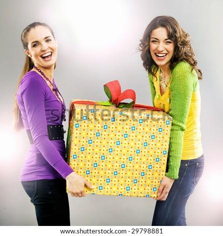 portrait of two happy beautiful girls holding a present - stock photo