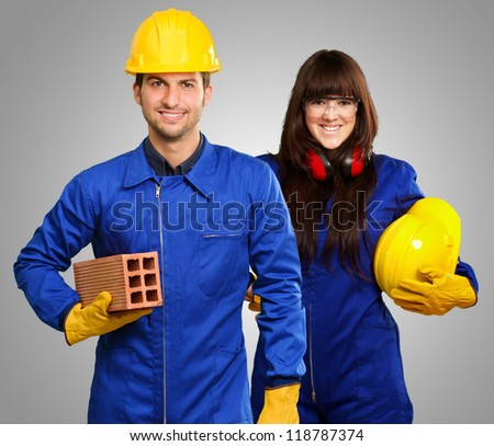 Portrait Of Two Happy Engineers Isolated On Green Background