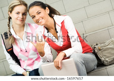 Portrait of two happy girls sitting on staircase and looking at camera