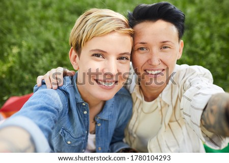 Portrait of two happy lesbians smiling at camera they taking selfie portrait while sitting outdoors Stockfoto ©