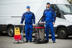 Portrait Of Two Happy Male Janitors Standing With Cleaning Equipment