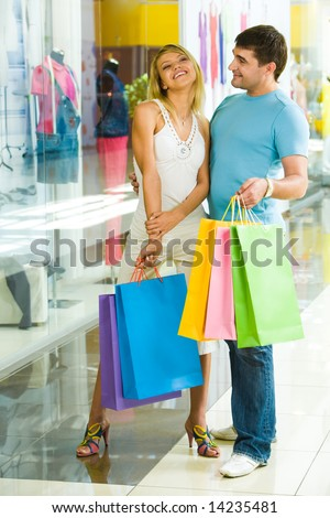 Portrait of two happy people holding bags and standing in the shopping center