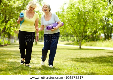 Portrait of two happy senior females walking down green grass - stock photo
