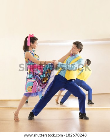 Portrait of two Happy teenage retro dance band on in very colorful dress on mirror reflection on wall background Two man and one woman full length looking at camera