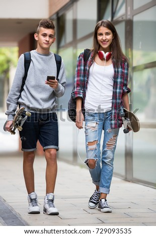 Portrait of two happy teenagers in casual walking by street with skateboards
