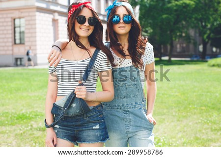 Portrait of two happy twins sisters stay together, wearing bright bandanas and stylish mirrored sunglasses, best fiend enjoy amazing time together.