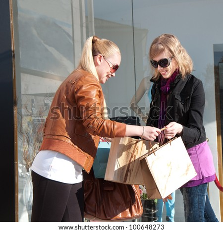 Portrait of two happy young women looking together in shopping bags