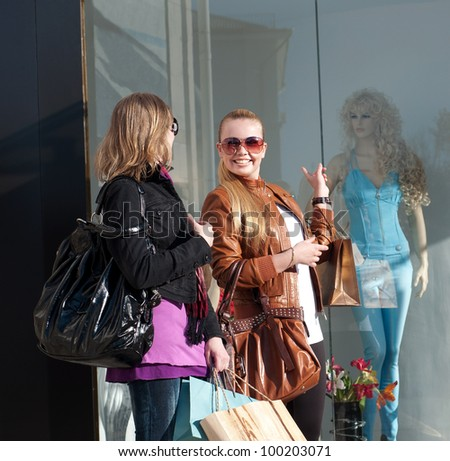 Portrait of two happy young women walking together with shopping bags