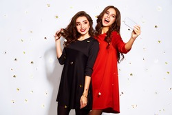 portrait of two happy young women who make selfie. in evening dresses on party over white background. firecrackers in the background.confetti.the concept party.funny faces