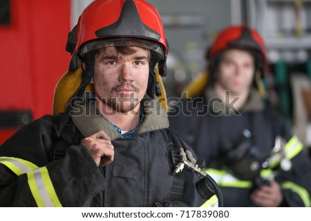 Portrait of two heroic fireman in protective suit and red helmet, second fireman is out of focus, closeup