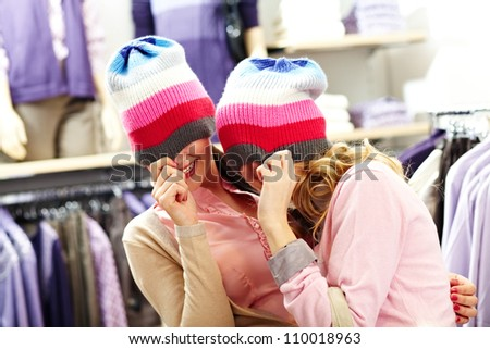 Portrait of two joyful girls with knitted caps on heads laughing in clothing department