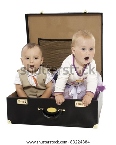 Portrait of two kids sitting in the suitcase