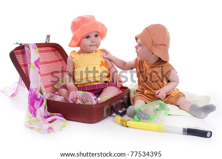 portrait of two kids with a large suitcase